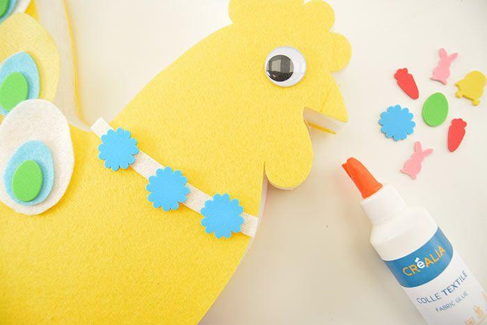 3. Créer un collier à la poule avec une longueur de feutrine pailletée puis coller 3 stickers adhésifs mousse «fleur».