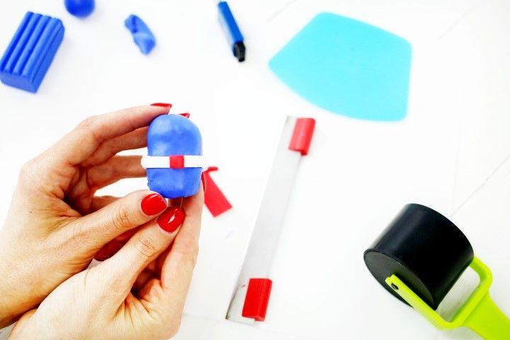 8.Décorer la ceinture avec un petit carré de pâte rouge découpé à l'aide du cutter
