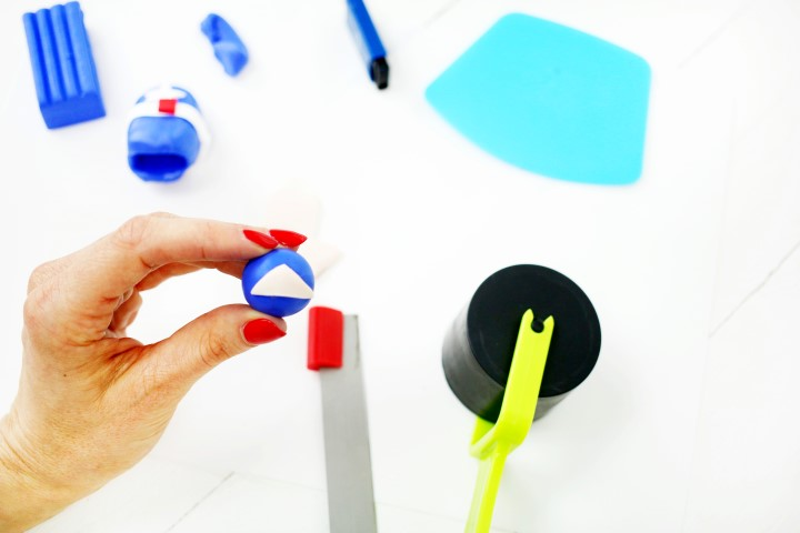 11. Dans la pâte couleur peau, découper un triangle et le placer sur la boule bleu. Cela donnera l'effet d'un masque.