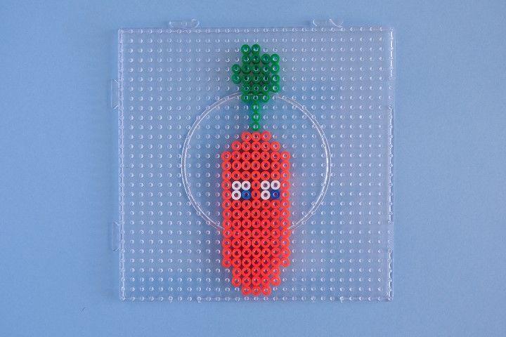 1. Réaliser un motif légume en suivant le modèle de la photos.  Positionner une perle sur chaque picot de la plaque.  Si besoin, une pince à épiler peut être utilisée pour faciliter le retrait des perles.
