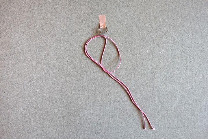 1. Couper le cordon de 1,70m en deux parties égales.  Placer un premier bout de cordon en le glissant à l'intérieur de l'anneau du porte-clé.