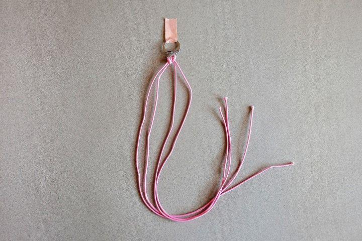 2. Nouer le second bout de cordon de la même façon que pour l'étape 1, sur l'anneau du porte-clés.  Les noeuds de macramé se réalisent grâce à 4 fils. On utilise les deux fils extérieurs que l'on noue autour des deux fils centraux.