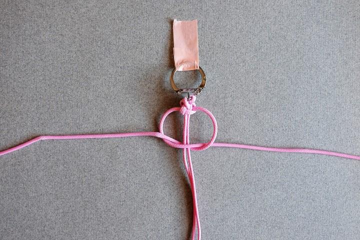 7. Introduire  le fil de droite dans la boucle formée sur la gauche, en passant par dessous les fils centraux. Tirer les deux fils extérieurs pour serrer le noeud autour des fils centraux.