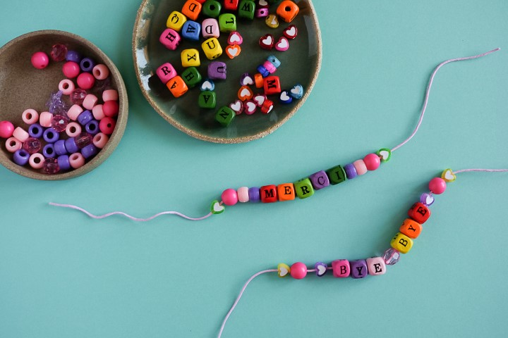 2. Enfiler les perles sur un cordon d'environ 20cm. Placer des perles avec un orifice de petit diamètre sur les extrémités afin de pouvoir bloquer les perles par un noeud simple de chaque côté.