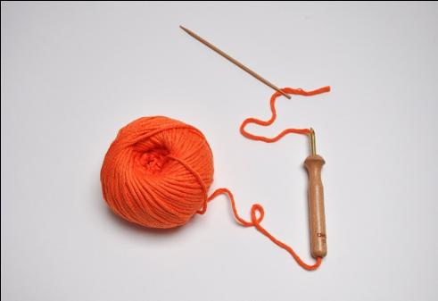 2. Enfiler le fil dans le chas de l'aiguille. Glisser l'aiguille dans la punchneedle de bas en haut. Faire ressortir l'aiguille par la pointe et la repasser dans le chas de la punchneedle. Enlever l'aiguille. La punchneedle est prête à être utilisée.