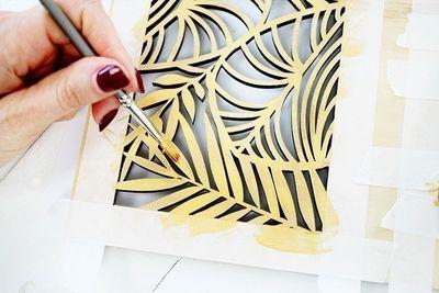 ETAPE 2/8 Peindre en doré le motif végétal à l'iade d'un petit pinceau rond. Pour créer un effet patiné, laisser le bois apparaître par endroit.