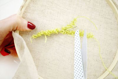 ETAPE 9/16 Pour changer de fil, piquer le punch needle dans la toile, la retourner et couper le fil le long de l'aiguille.