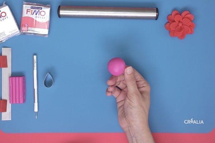 ETAPE 1 Couper un demi pain de pâte Fimo® et le modeler entre les mains pour chauffer la pâte et former une boule.