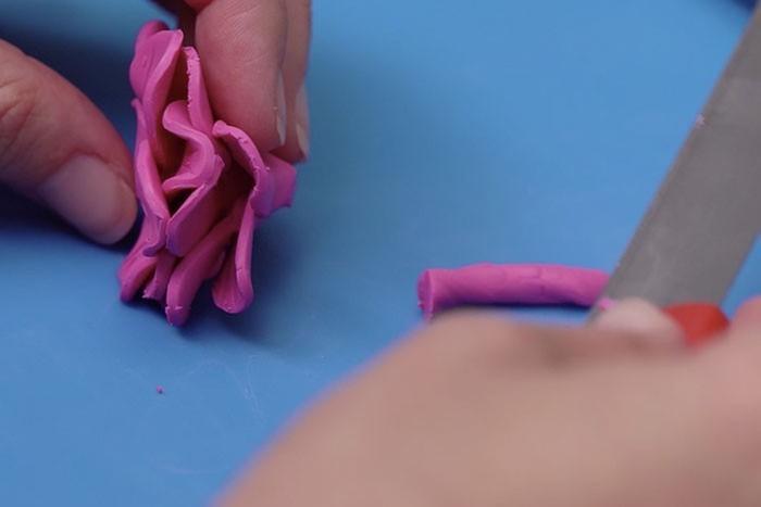 ETAPE 6 Couper l'extrémité pointue avec une lame de cutter pour créer un socle plat à la fleur.