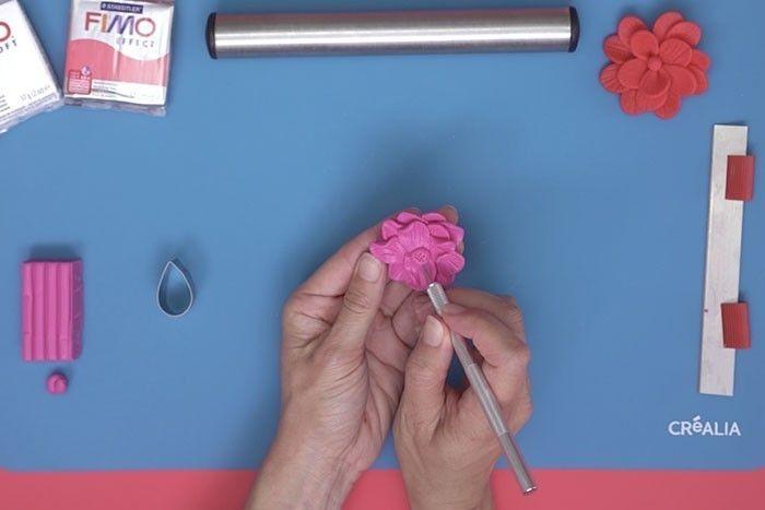 ETAPE 7 Avec l'excédent de pâte, modeler entre les doigts une petite boule de pâte pour créer le cœur de la fleur et la texturer de petits points avec le pic métal.