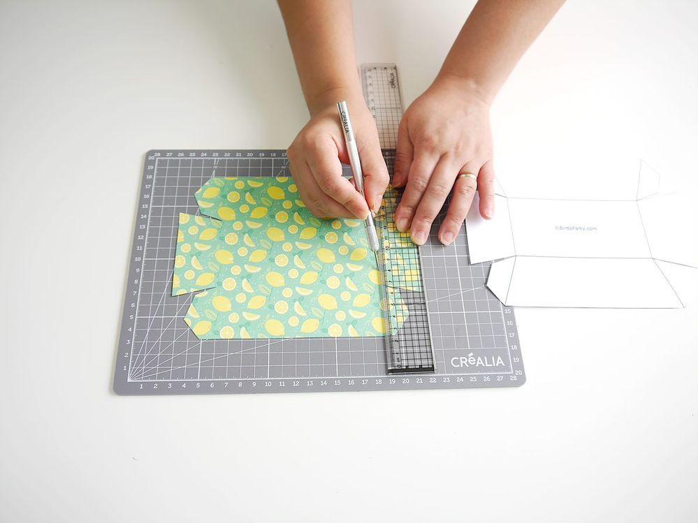 3. Utiliser une règle et l'outil de pliage pour marquer les plis de la boîte, selon les tracés du gabarit.