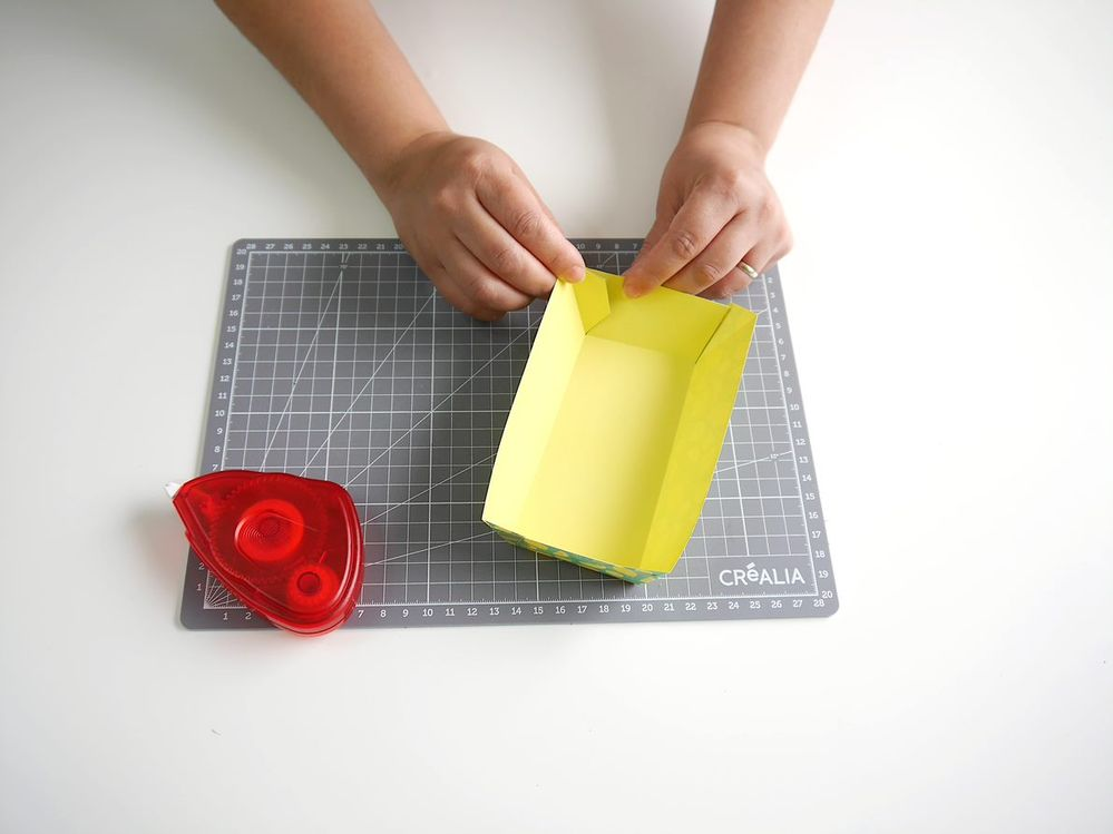 5. Utiliser l'adhésif double face pour coller les rabats sur les côtés de la boîte. Remplir les boîtes avec des bonbons, ou autres friandises.