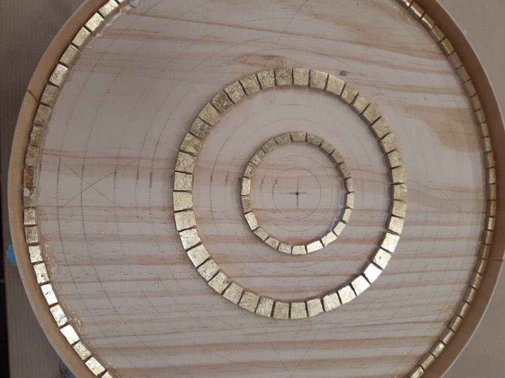 On commence par faire ces lignes de tesselles à la feuille d'or. Attention plus vous allez vers le centre, plus il faudra les tailler en forme de trapèze pour obtenir un cercle bien rond.