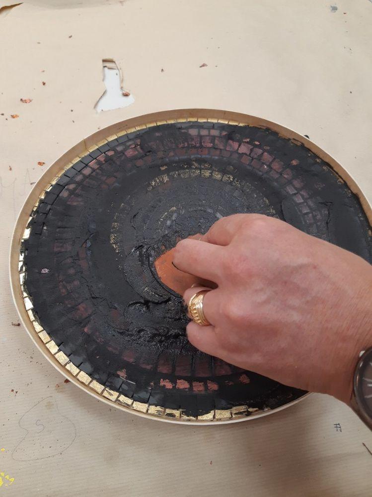 Preparer le joint, ici gris pour faire ressortir les couleurs. Dans un petit bac en plastique mélanger quatre part de joint pour une part d'eau. Appliquer le joint avec l'esteque sur la mosaïque et boucher toutes les interstices. Retirer le maximum de joint. S'il en reste trop, c'est galère à enlever.