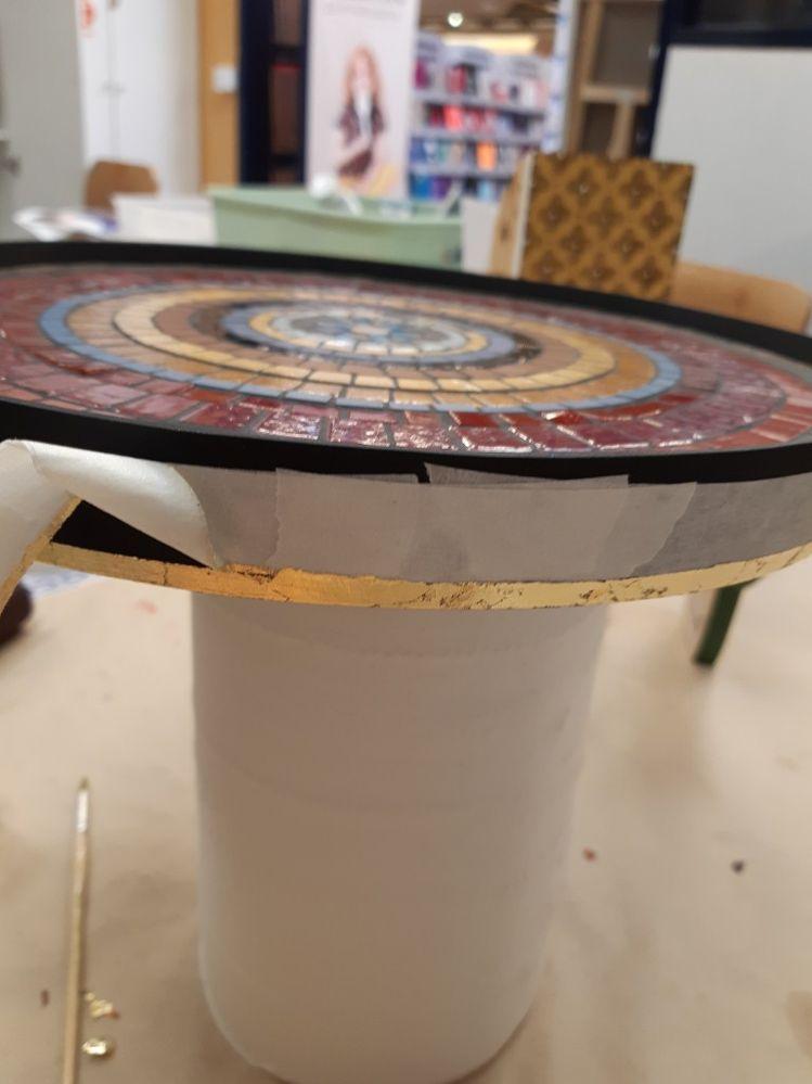Peindre les bords et le dessous du plateau, ici en noir, et les pieds (noir et rouge mélangés) . J'ai fait un liseré de feuille d'or en rappel sur le bord exterieur du plateau ainsi que sur le haut des pieds. Pour finir vernir.