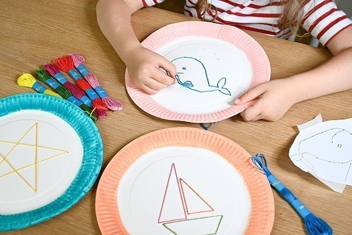 ETAPE 3/4 Couper des longueurs de fil à broder de couleur, les enfiler sur une aiguille à bout rond. Broder les motifs en passant dans chaque trou et nouer les fils au dos de l'assiette.