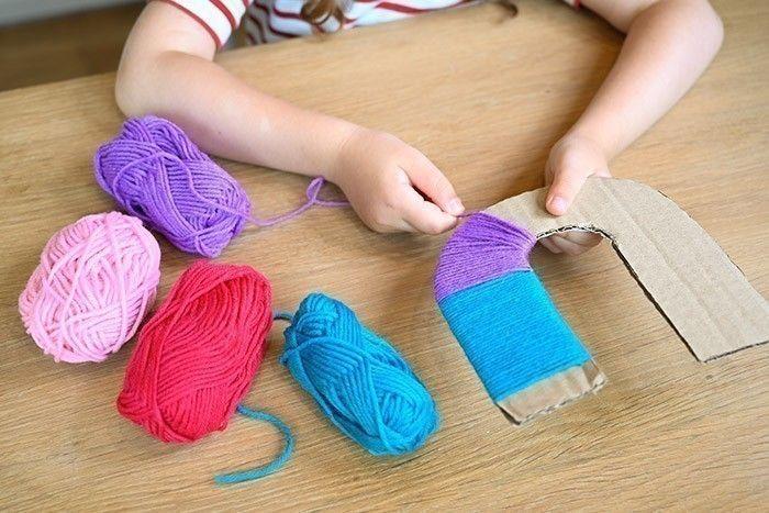 ETAPE 2/4 Entourer plusieurs couleurs de fil de laine et nouer au dos.