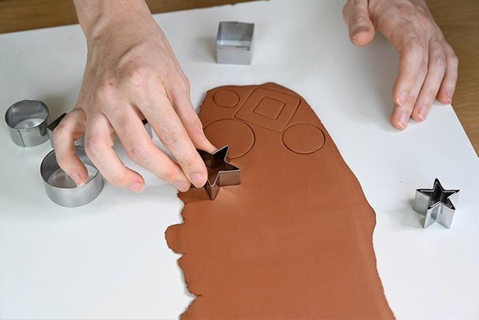 ETAPE 2/6 Découper à l'aide des emportes pièces différentes formes. En évider certaines. Créer ces billes quelques billes d'argile.
