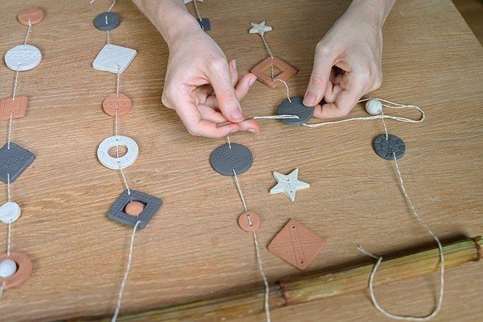 ETAPE 5/6 Disposer les différentes pièces pour créer une composition harmonieuse. Couper différentes longueurs de ficelle bicolore et enfiler les pièces d'argiles. Suspendre le tout sur une branche ou un bambou.