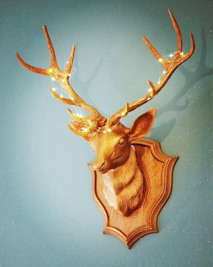 Trophée tête de cerf de récupération bombé en doré et mis en lumière avec une mini guirlande