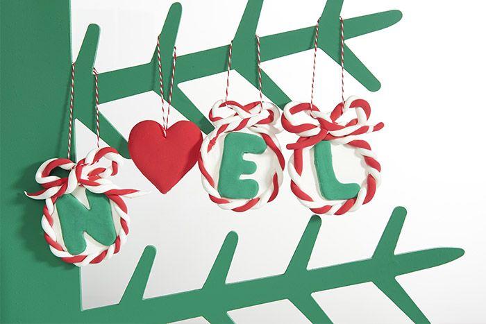 5. Insérer une longueur de ficelle bicolore dans les boucles des boules pour les suspendre au sapin de Noël. Pour le cœur, réaliser un trou à l'aide d'un pic métal ou d'une aiguille avant d'y enfiler une longueur de ficelle.