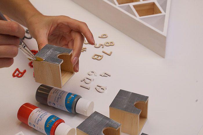 3. Pour créer un effet patiné sur les éléments gris, enduire légèrement le pinceau plat de peinture blanche et effleurer la face des tiroirs et numéros.