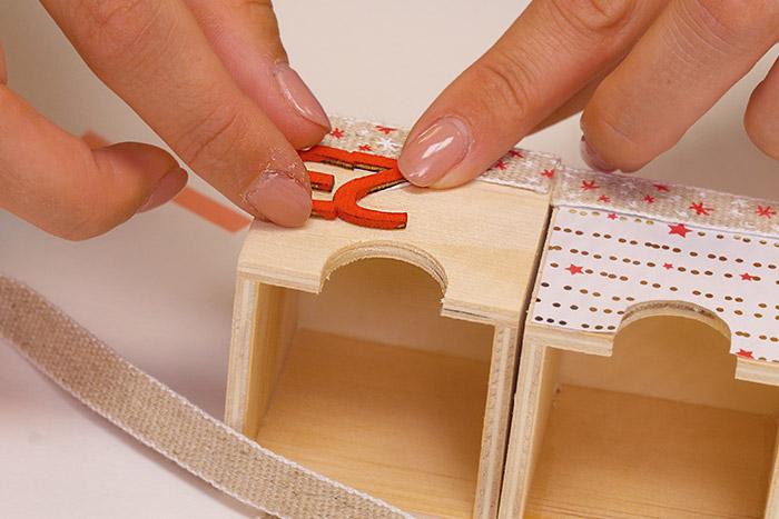 6. Décorer certains tiroirs de morceaux de ruban. Coller les numéros de l'Avent et replacer les tiroirs dans le calendrier.