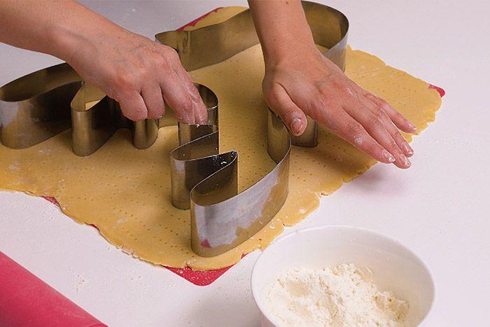 2. Fariner le plan de travail et étaler la pâte à l'aide d'un rouleau. Piquer la pâte avec une fourchette. Presser l'emporte-pièce XXL renne et retirer l'excédent de pâte. Cuire environ 12 à 15 minutes à 180°C dans un four préchauffé : le biscuit est doré une fois cuit. Laisser refroidir.