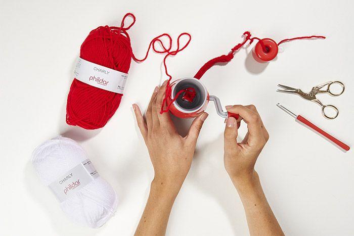 1. Insérer le fil de laine dans le tricotin et commencer à tricoter. Pour réaliser les différentes formes, prévoir : • Etoile : 40 cm de tricotin • Cœur : 30 cm de tricotin • Mot Noël : 70 cm de tricotin • Renne : 90 cm de tricotin