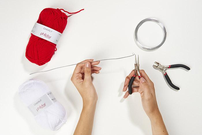 2. Couper une longueur de fil aluminium avec la pince coupante correspondant à la longueur de la forme choisie. Arrondir une extrémité du fil d'aluminium à l'aide de la pince à bijoux ronde et créer une boucle dans l'autre extrémité.