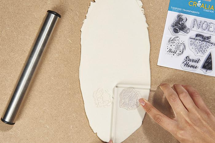 2. Positionner un tampon transparent sur le bloc acrylique et tamponner l'argile auto-durcissante avec différents motifs.