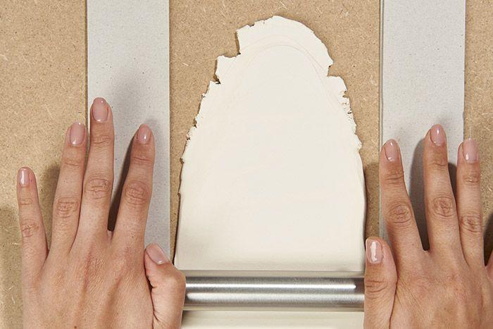 1. Etaler l'argile auto-durcissante sur une planche en bois à l'aide d'un rouleau. Astuce : Pour obtenir une épaisseur égale, positionner deux planchettes de chaque côté du rouleau.