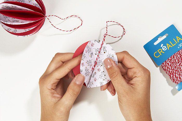 6. Couper une longueur de ficelle bicolore, la coller au cœur de la boule et fermer la boule avec un dernier point de colle.