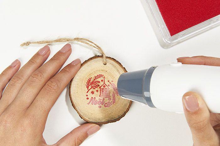 6. Chauffer le motif avec l'embosseur électrique : la poudre fond et laisse apparaître le motif avec une surbrillance. Répéter les actions précédentes au dos du rondin
