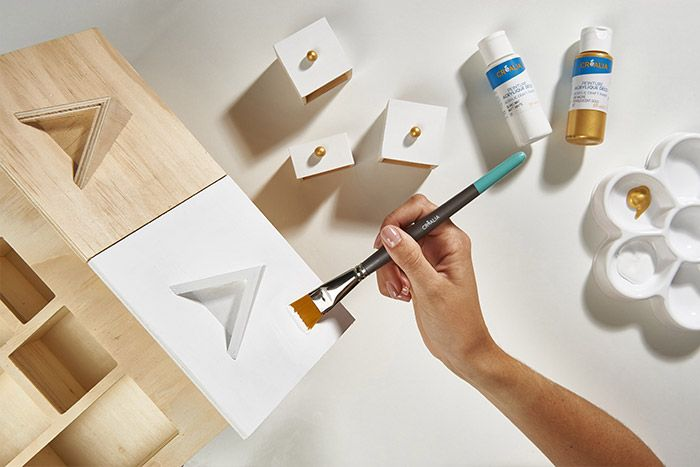 1. Peindre tous les boutons en doré. Laisser sécher. Peindre quelques tiroirs et tout le toit en blanc. Protéger avec du ruban de masquage si besoin. Laisser sécher.