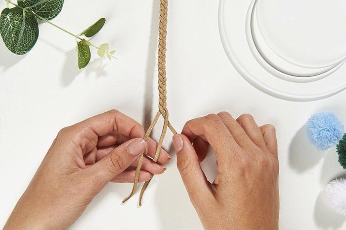 1. Diviser la bobine de fil suédine en trois longueurs égales et tresser. Astuce : agrafer la tresse aux extrémités pour un meilleur maintien en attendant d'être collée. Une bobine permet de réaliser deux couronnes de 10 cm et une couronne de 15 cm.