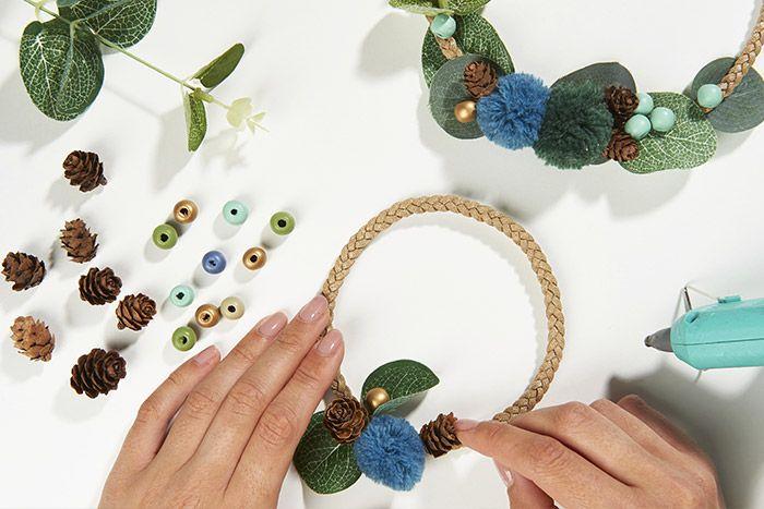 3. Décorer les mini couronnes avec différents éléments : pompons, mini pomme de pin, perles en bois, baies dorées et feuilles d'eucalyptus.