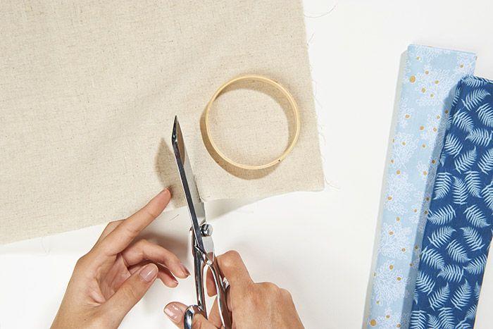 1. Positionner le cercle en bois du mini tambour sur le tissu et couper un carré tout autour en laissant une marge suffisante.