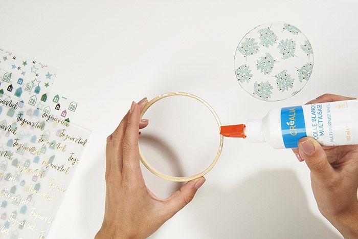 2. Encoller le dos du cercle en bois et le poser sur la face du rond de papier calque découpé précédemment. Ce dernier doit être positionné en arrière-plan. Laisser sécher.