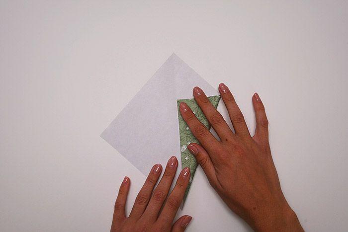 2. Rabattre les angles opposés vers la diagonale, comme pour former un cerf-volant et plier.