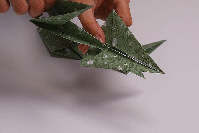 7. Pour former l'étoile, insérer la petite pointe de la première branche sous les plis de la grande pointe de la deuxième branche pour la maintenir. Répéter cette action jusqu'à former toute l'étoile avec toutes les branches restantes.