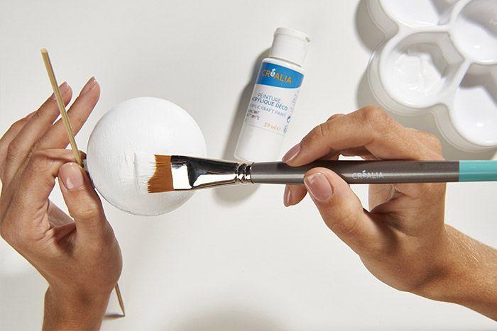2. Recouvrir l'extérieur de la boule avec la peinture blanche. Laisser sécher.
