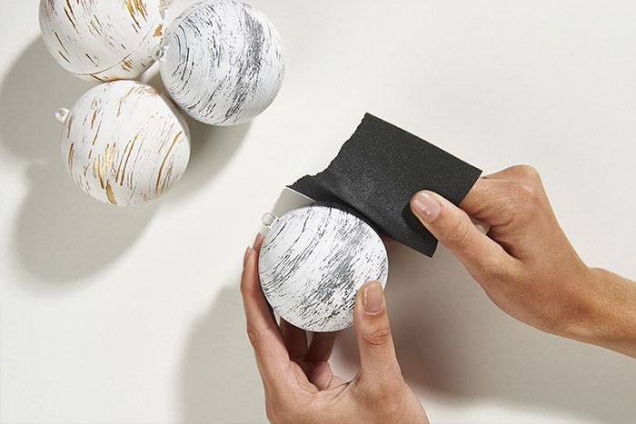 3. Pour obtenir l'effet écorce de bouleau, poncer horizontalement l'extérieur de la boule, de façon irrégulière, pour faire apparaître la couleur intérieure de la boule.