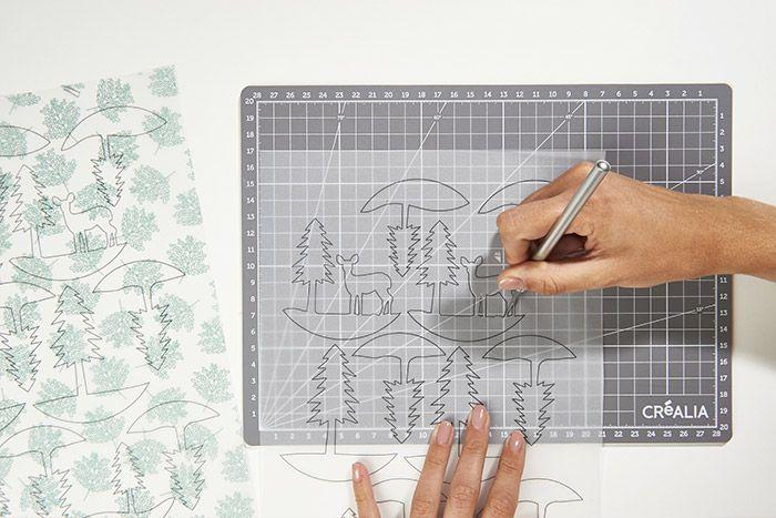 1. Télécharger et imprimer le gabarit sur les papiers calques imprimés de la collection et une feuille de papier calque unie. Découper minutieusement les motifs à l'intérieur des traits noirs.