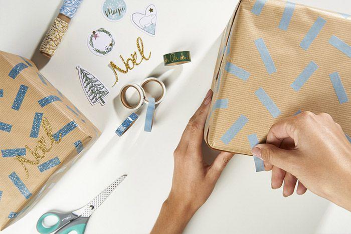 Idée n°1 : Emballer les cadeaux avec du papier kraft. Découper des morceaux de masking tapes pour donner un rendu graphique aux paquets. Coller le mot Noël pour finaliser la décoration.