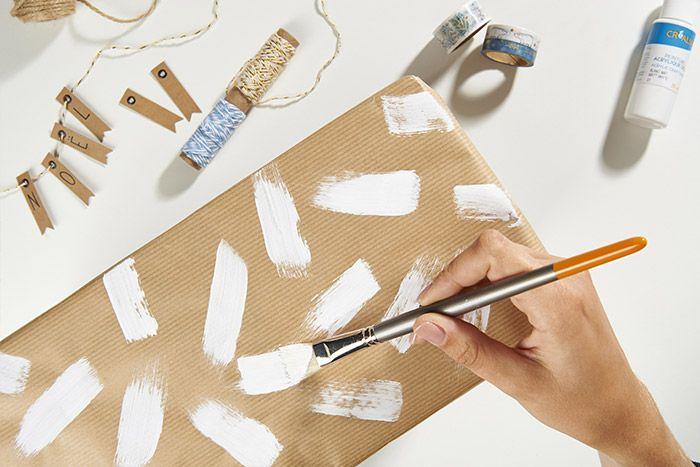 Idée n°2 : Emballer les cadeaux avec du papier kraft. Enduire un pinceau plat soie de porc de peinture blanche et peindre des trainées sur tout le paquet. Laisser sécher. Finaliser l'emballage avec des étiquettes kraft et de la ficelle.