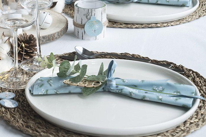 Se servir des tissus de la collection pour créer une serviette ou une pochette à couverts. Le fermer avec un ruban et insérer une branche d'eucalyptus et un accessoire décoratif.