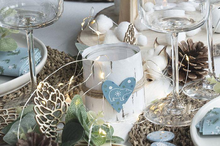 Pour créer un photophore de table, récupérer un pot de yaourt en verre et découper une bande de papier dans la ramette aux dimensions du pot en verre. L'enrouler et la coller autour du pot, enrouler une longueur de ficelle naturelle et coller un accessoire décoratif. Insérer une bougie led dans le pot pour finaliser le photophore
