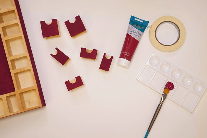 Peinture du calendrier de l'Avent 1. Peindre le contour, le fond du support et quelques tiroirs avec la peinture prune. Positionner du ruban de masquage si besoin.
