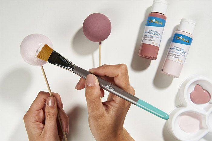 1. Peindre les boules polystyrène avec les couleurs rose poudré, vieux rose et doré. Laisser sécher puis insérer les attaches métalliques. Astuce : S'aider d'un pic en bois pour peindre facilement.